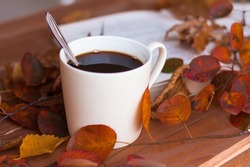Autumn, autumn leaves, a hot steaming Cup of coffee and an old book and a grey scarf on the background of a wooden table. Seasonal, morning coffee, Sunday relaxation and still life concept.