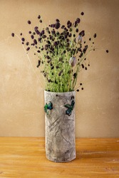 Autumn awesome still life with Sanguisorba officinalis and poppy heads  in handmade ceramic vase with green dragonflies placed on wooden board in front of brown wall with clay plaster