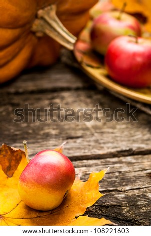 Autumn background with apples, pumpkin and maple leaf on old wooden table. Thanksgiving day concept. Shallow depth of fields
