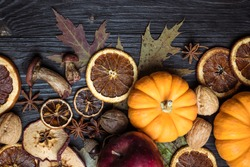 Autumn background with dried fruits, oranges, apples, nuts, anise, mushrooms, acorns and pumpkin. Dry tree leaves. Natural wooden background. Flat lay, top view, copy space. Happy Thanksgiving Day.