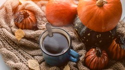 Autumn background with dry leaves, blue cup of coffee. Knitted background, pumpkins, October, November. Autumnal atmosphere. Autumn season.