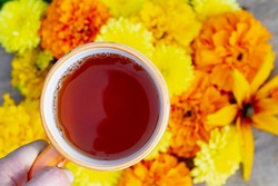 Autumn background with flower tea in an orange Cup and autumn yellow flowers, a Man holding a Cup with a hot drink in his hand. Copy space.