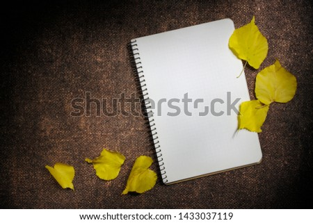 Autumn background with yellow leaves and notepad, white sheet of paper on a bronze fabric, open sketchbook for notes or drawings, the concept of the beginning of the school season, top view