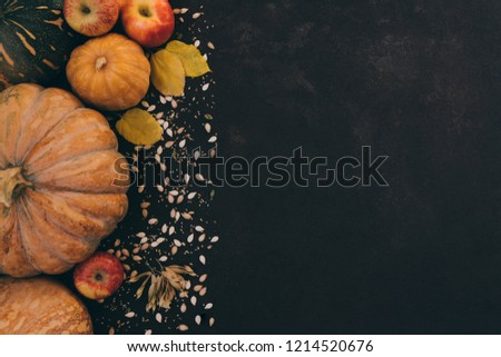 Autumn background with yellow leaves, red apples and pumpkins. Border of fall harvest on aged wood with copy space. Mockup for seasonal offers and autumn food, Top view with copy space. Toned image.