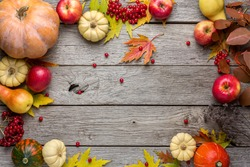 Autumn background with yellow maple leaves, red apples and pumpkins. Frame of fall harvest on aged wood with copy space. Mockup for seasonal offers and holiday post card, top view