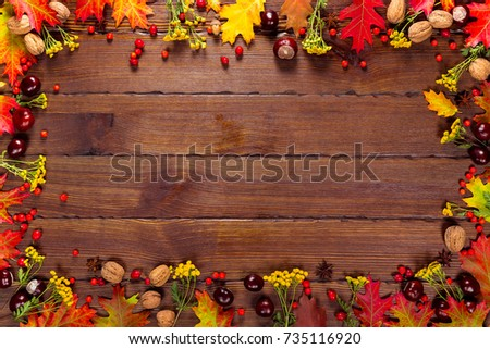 Autumn background with yellow, with bright leaves, pine cones, chestnuts and berries. Frame autumn harvest on seasoned wood with free space. The layout offers and seasonal holiday card #735116920