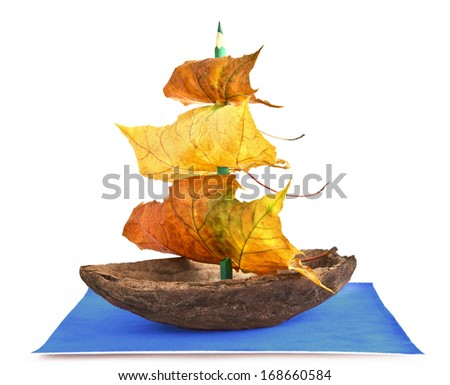 Autumn boat from the shell of cocoa bean with a mast pencil and sails of maple leaves on a velvet blue sheet