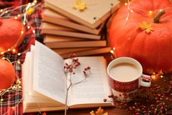 Autumn books.Autumn cozy  reading. Books and a cup of tea, a checkered scarf, a large orange pumpkin, red berries and a shining garland on a wooden table.NaNoWriMo Writing Autumn Marathon.
