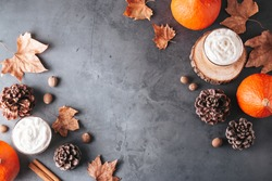 Autumn border with natural pine cones, pumpkins, dried leaves and pumpkin latte on dark grey stone top, top view, copy space. Fall, Thanksgiving background, cozy flat lay