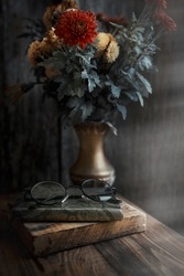 autumn bouquet of flowers is on the table next to glasses and a book