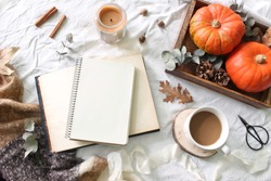 Autumn breakfast in bed composition. Blank notepad, book mockup. Coffee, candle,eucalyptus leaves and pumpkins on wooden tray. White linen bed sheet background. Thanksgiving, halloween. Flat lay, top.