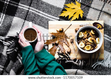 Autumn breakfast with coffee and flakes. A cup with a drink in the hands of a girl. Cozy atmosphere with a blanket in the cell.