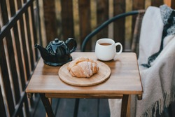 Autumn breakfast with hot tea and croissants on a cozy wooden balcony of a log cabin. Fall atmosphere. Slow living concept.