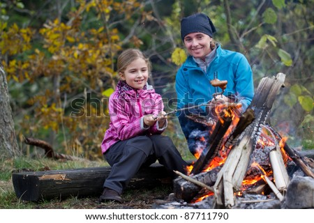 Autumn campfire - Mother and daughter are baking sausages at the bonfire