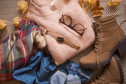 Autumn clothing outfit with sweater, jeans and boots, top view of fall/winter season outfit idea with glasses and watch accessory