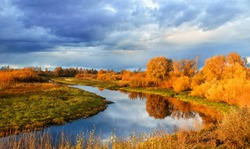 Autumn colored forest view - sunset picturesque landscape with river and yellowed autumn trees in the evening. Soft filter applied.