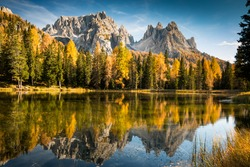 autumn colorful dolomites mountain peaks in italy with blue sky reflecting in the lake