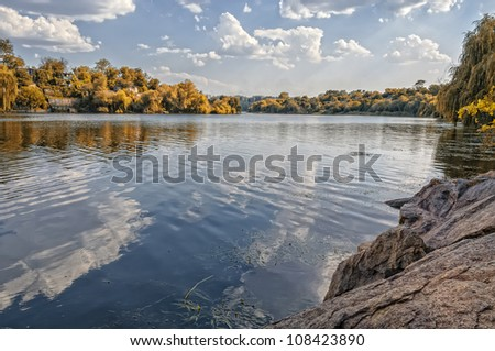 Autumn colorful foliage over lake with beautiful woods