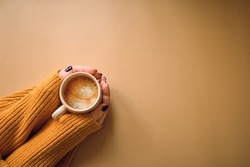Autumn composition. Cup of coffee and with woman's hand, yellow sweater on pastel yellow background. Autumn, fall concept. Flat lay, top view, copy space