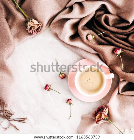 Autumn composition. Cup of coffee, autumn dry leaves and roses on a light background. Flat lay, top view, copy space