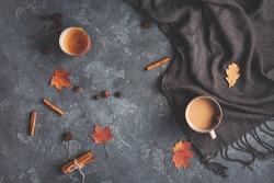 Autumn composition. Cup of coffee, blanket, dried autumn leaves, cinnamon sticks on black background. Flat lay, top view