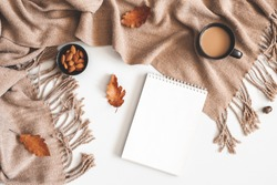 Autumn composition. Cup of coffee, plaid, notepad, autumn leaves on white background. Flat lay, top view, copy space