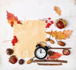 Autumn composition. empty Paper blank, black retro alarm clock, leaves, acorns, berries, branch, nut, cone, chestnut. fall harvest season, thanksgiving, halloween, business concept. copy space