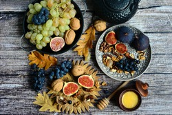 Autumn composition. Figs, grapes, walnuts and autumn leaves on a wooden background, top view.