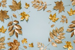 Autumn composition. Frame made of autumn golden  leaves on blue background. Flat lay, top view, copy space
