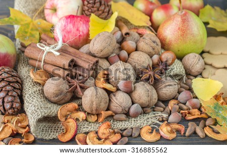 Autumn composition of fruits, nuts and spices - apples, pears, walnuts, pine nuts, hazelnuts, cinnamon and star anise. Selective focus