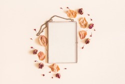 Autumn composition. Photo frame, dried flowers and leaves on pastel beige background. Autumn, fall concept. Flat lay, top view, copy space