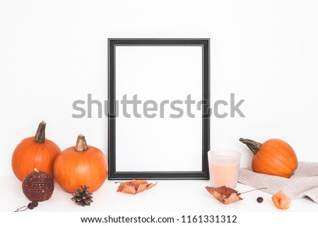 Autumn composition. Photo frame, pumpkins, candles, dried leaves on white background. Autumn, fall, halloween concept. Front view, copy space