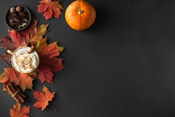 Autumn composition - Pumpkin Spice Latte, autumn maple leaves and pumpkins  on black background, creative flat lay, top view, copy space. Seasonal autumn concept with coffee drink.