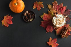 Autumn composition - Pumpkin Spice Latte,  maple leaves and pumpkin on black background, creative flat lay, top view, copy space. Seasonal autumn concept with coffee drink.