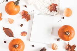Autumn composition. Pumpkins, candles, dried leaves, notebook, plaid on white background. Autumn, fall, halloween concept. Flat lay, top view, copy space
