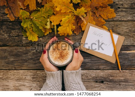 Autumn composition still life. Woman's hands with cup of coffee, cappuccino, latte coffee. autumn leaves, craft envelope and paper with eriitern Hello Autumn phrase on vintage background. Hot drink