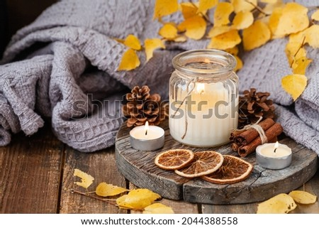 Autumn composition with aromatic candle, dry citrus, cinnamon. Aromatherapy on a grey fall morning, atmosphere of cosiness and relax. Wooden background close up
