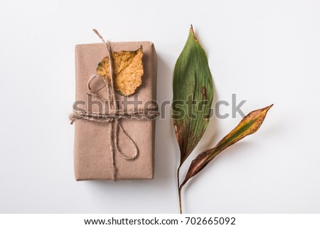 Autumn composition with handmade gift in craft paper with autumn dry green leaf of white. Top view. Flat lay.