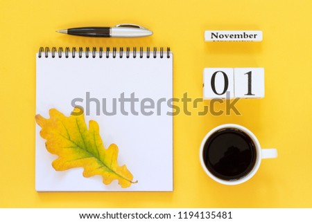 Autumn composition. Wooden calendar November 1 coffee cup, empty open notepad with pen and yellow oak leaf on yellow background. Top view Flat lay Mockup Concept Hello November