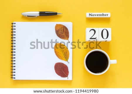 Autumn composition. Wooden calendar November 20 cup of coffee, empty open notepad with pen and yellow oak leaf on yellow background. Top view Flat lay Mockup Concept Hello November