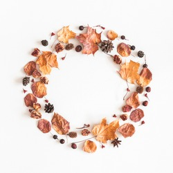 Autumn composition. Wreath made of autumn dried leaves, berries, acorns on white background. Flat lay, top view, copy space, square