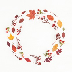 Autumn composition. Wreath made of autumn flowers and leaves on white background. Flat lay, top view, copy space.