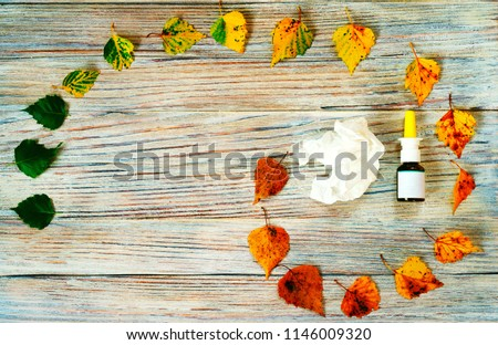autumn concept, the transition from green summer leaves to yellow swollen and runny nose with drops a paper handkerchief