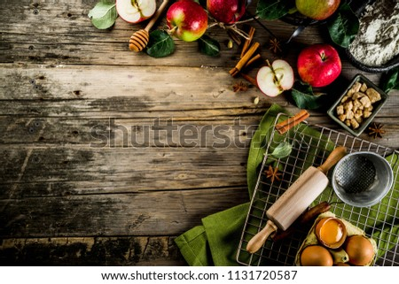 Autumn cooking background, Apple pie baking concept, fresh red apples, sweet spices, sugar, flour, rolling pin, eggs, baking utensils, wooden background copy space