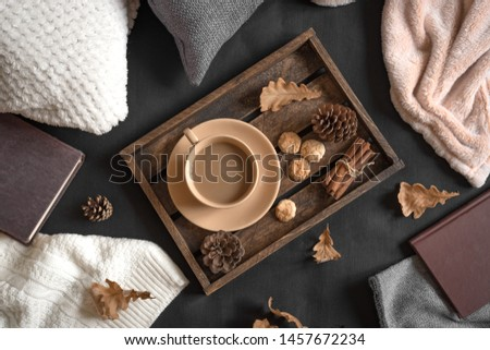 Autumn coziness concept. Seasonal autumnal composition with soft plaid, coffee and book. Cozy home and hygge concept. #1457672234