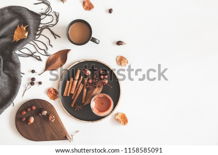 Autumn cozy composition. Cup of coffee, plaid, candle, dried leaves on white background. Autumn, fall concept. Flat lay, top view, copy space
