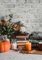 Autumn cozy home still life. Pumpkin, stack of books, burning candle, pile of winter autumn sweaters, jar of marshmallows, cup, teddy bear on the kitchen table. Flat lay