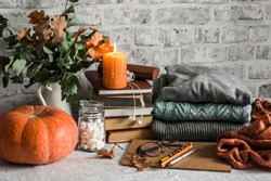 Autumn cozy home still life. Pumpkin, stack of books, burning candle, pile of winter autumn sweaters, jar of marshmallows on the kitchen table. Flat lay