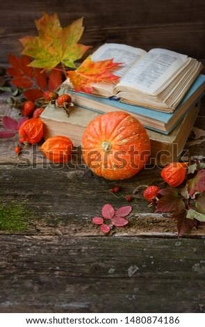autumn cozy still life with pumpkin. orange pumpkin, autumn leaves and old books on rustic wooden background. autumn atmosphere composition. fall season. copy space #1480874186