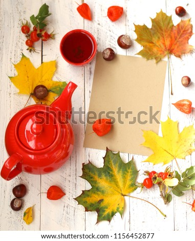 Autumn cozy tea drinking.red teapot, cup with tea, maple bright leaves, chestnuts, dogrose on shabby chic background.Autumn season.Autumn time